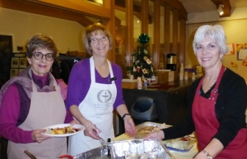 Fellowship Committee members serving turkey and gravy at Second Unitarian's annual Thanksgiving Dinner.