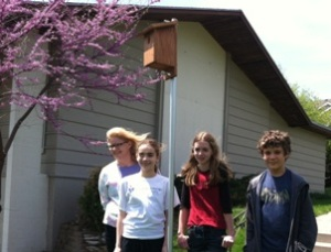 Teens standing around their finished birdhouses