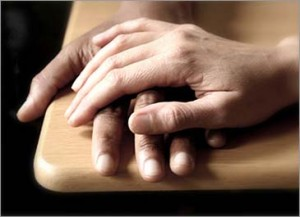 A person's hand resting on another's in a show of compassion.