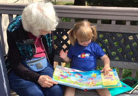 Church member reading to young child during annual book fair
