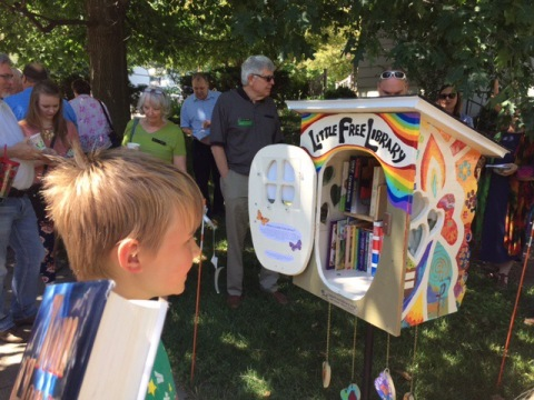 Children and adults admiring the colorful little free library