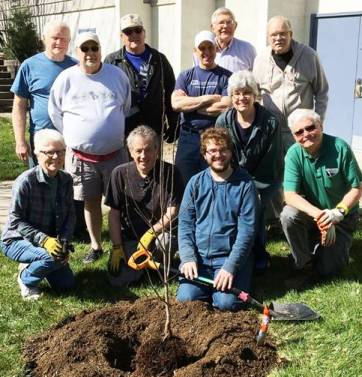 Participants of church clean-up day gather around a tree they have planted