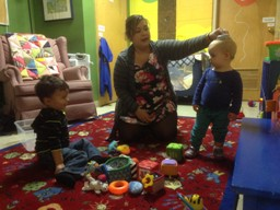 two toddlers and a care provider playing in the nursery