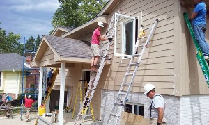 Workers finishing siding on front of home