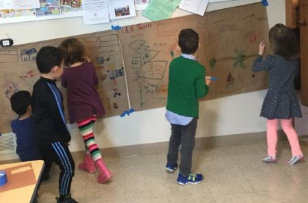 Children drawing on a wall mural during Children's Sunday morning religious education.